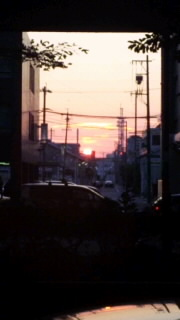 ビルの谷間に沈む夕陽